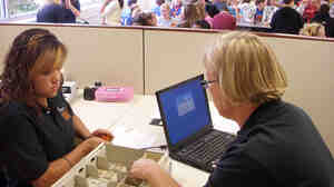 Business teacher Glenda Head, right, and student Kiana Anorve count money.
