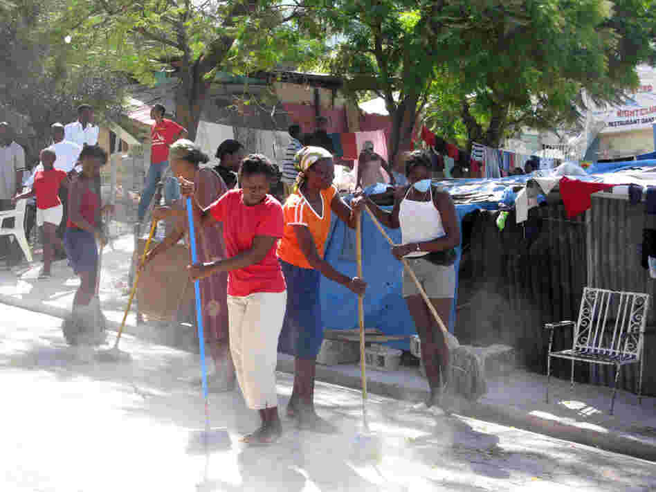 Women sweep the street in an impoverished area outside of Port-au-Prince, Haiti.