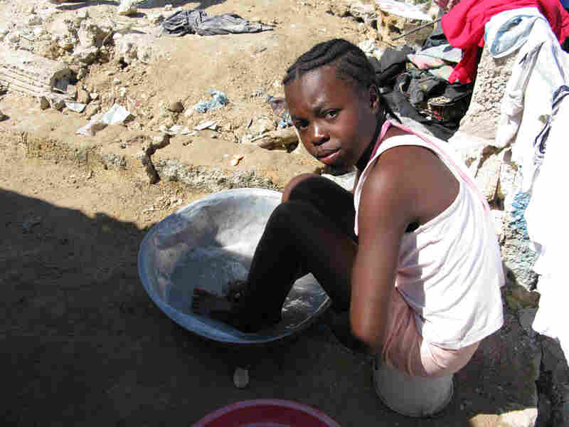 A little girl washes herself with soapy water in an encampment built by survivors in Haiti.