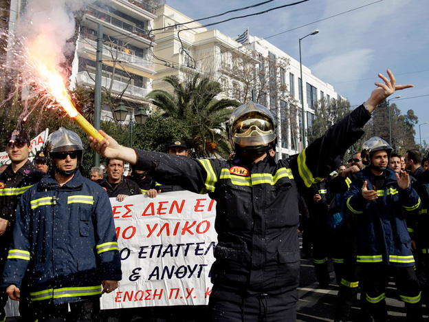 A firefighter holds a flare as others chant slogans outside the Greek parliament during a protest in central Athens last month. About 2,000 firefighters demonstrated against planned spending cuts by the center-left government, which is struggling to reform Greece's debt-ridden economy and plug a vast budget deficit. Prime Minister George Papandreou has ruled out pay increases for most civil servants this year, citing the state of the public finances, and says public sector hirings will be limited.
