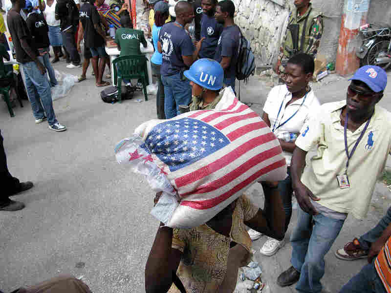 A woman carries off a 55-pound sack of rice given out in Port-au-Prince, Haiti, on Sunday.