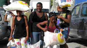 Women struggle to carry 55-pound bags of rice given out Sunday in Port-au-Prince, Haiti.
