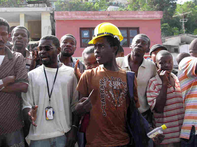 An angry young man shouts at an organizer during food distribution in Port-au-Prince.