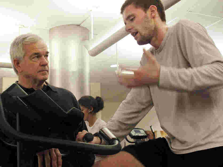 Exercise researcher Bob Karch coaches a man working out on the bike.