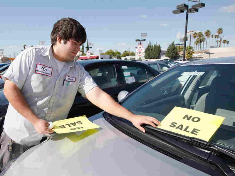 "Raul Quecada places a ""No Sale"" sign on a used Toyota vehicle."