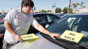 """Raul Quecada places a """"No Sale"""" sign on a used Toyota vehicle."""
