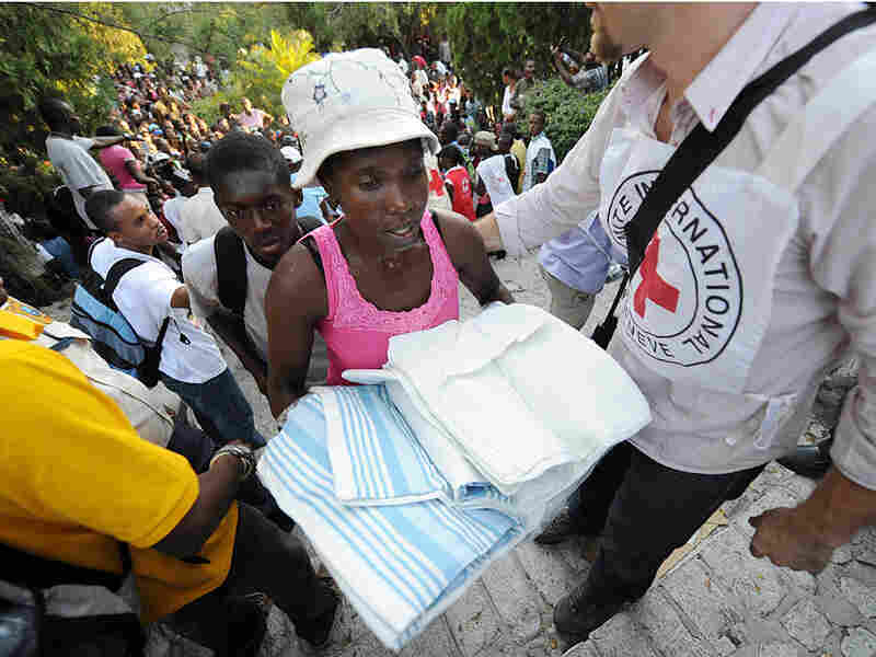 A Haitian woman receives bedding from the Red Cross