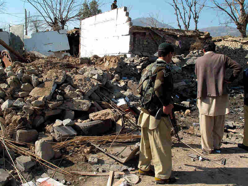 Soldiers of Pakistan's paramilitary force look at bomb damage.
