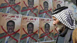 Iraqi man walks past posters for a Sunni lawmaker in January.