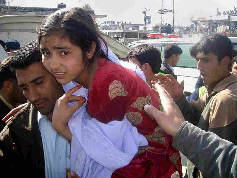 A man carries an injured girl from the site of a bombing in Timergara