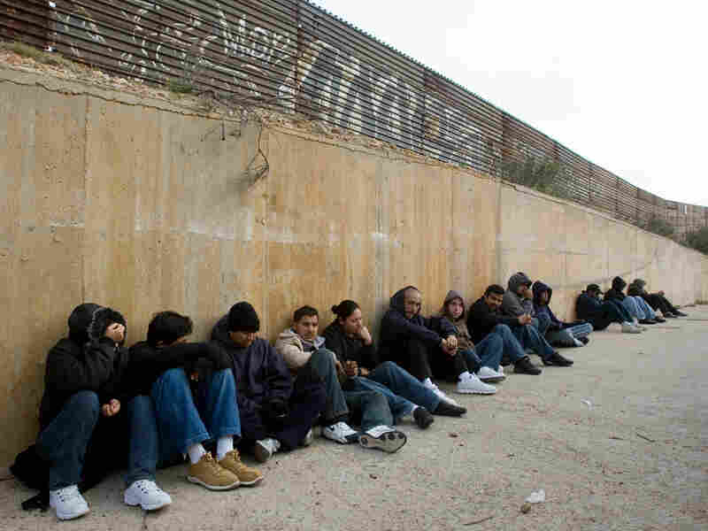 People waiting to cross illegally into the U.S. sit along the border fence in Tijuana in 2008.
