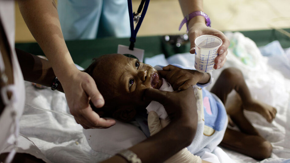 Doctors from the University of Miami's Global Institute for Community Health and Development tend to a baby at a field hospital in Port-au-Prince.