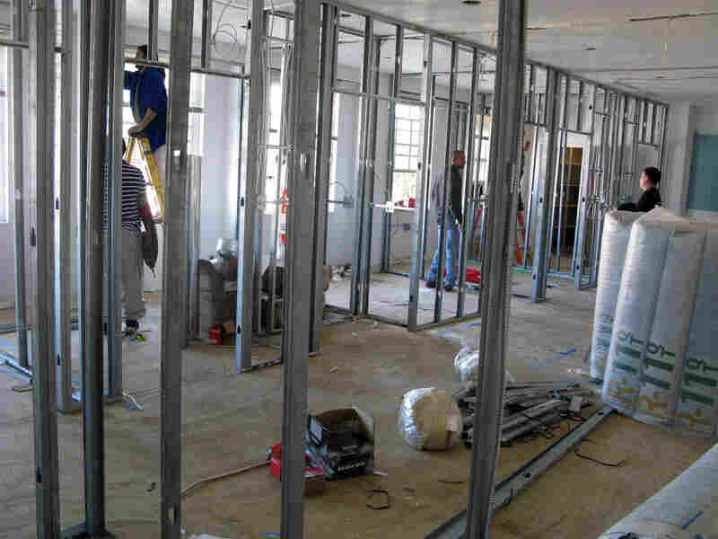 Construction workers convert Sunday School rooms into exam rooms.