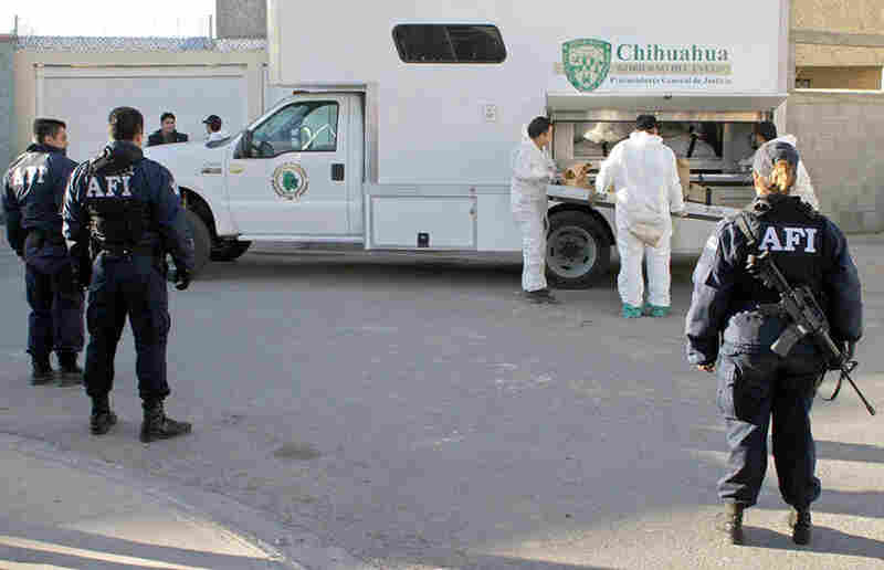 Mexican law enforcement officials load a corpse found at a Juarez drug cartel's house in 2004.