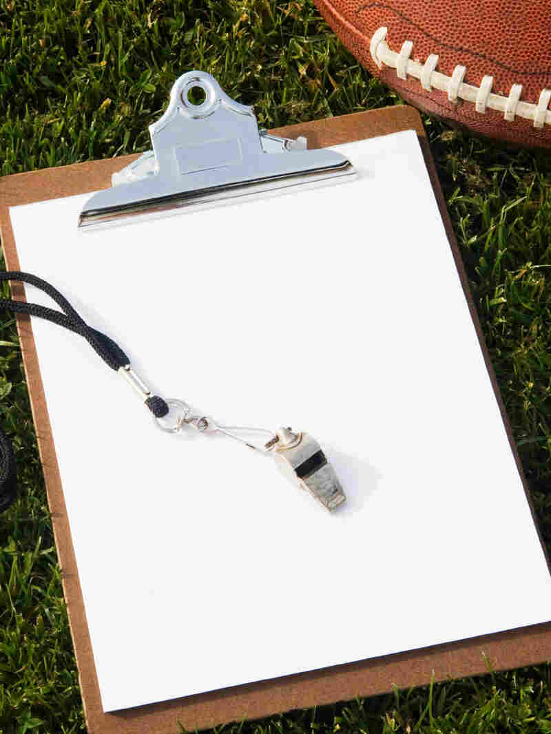 A football, clipboard, and whistle laying on the grass
