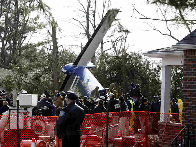 Workers clear debris from the crash site of Continental Connection Flight 3407 in Clarence, N.Y., Fe