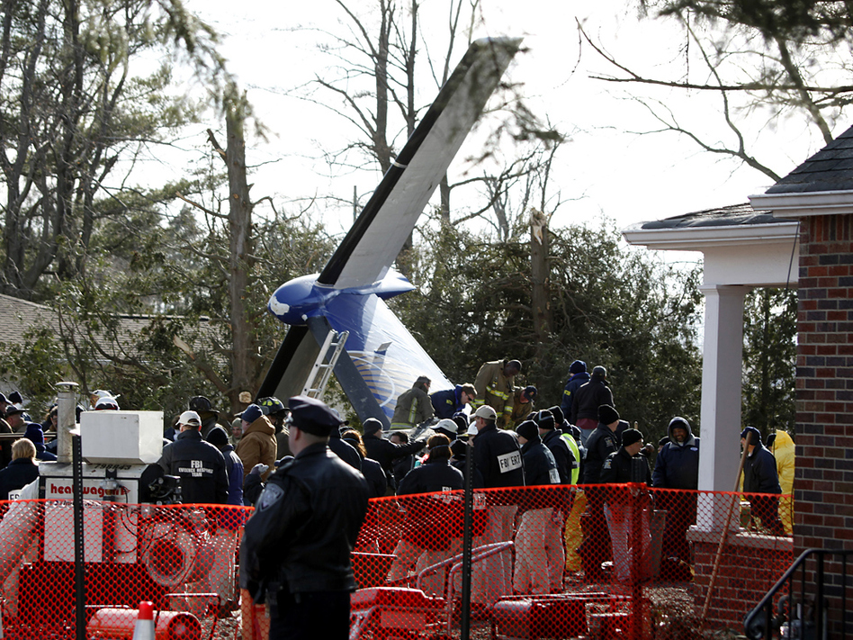 Workers clear debris from Continental Connection Flight 3407, which crashed Feb. 12, 2009, in Clarence, N.Y. The plane crashed as it approached the Buffalo airport, killing all 49 people on board and one on the ground.