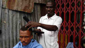 Barber Luxon Fanfan cuts customer Cadelis Dennis' hair outside.