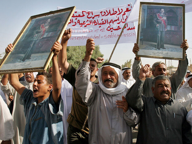 Iraqis holding pictures of Saddam Hussein march during a protest against the new constitution of Iraq near Ramadi in 2005.