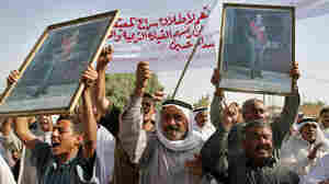 Iraqis holding pictures of Saddam Hussein march during a protest.