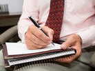 A  doctor takes notes on a writing pad.