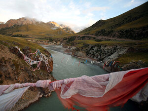 Tibetan prayer flags hang from a bridge crossing the Mekong River at sunrise.