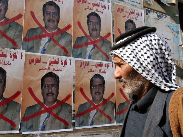 An Iraqi man walks past posters with a symbolic X across a picture of Iraqi lawmaker Dhafir al-Ani, a Sunni politician who was barred from running in the election because of alleged ties to the Baath party.