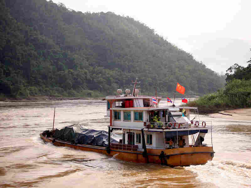 In Myanmar, a cargo ship heads upstream toward China on the Mekong River.