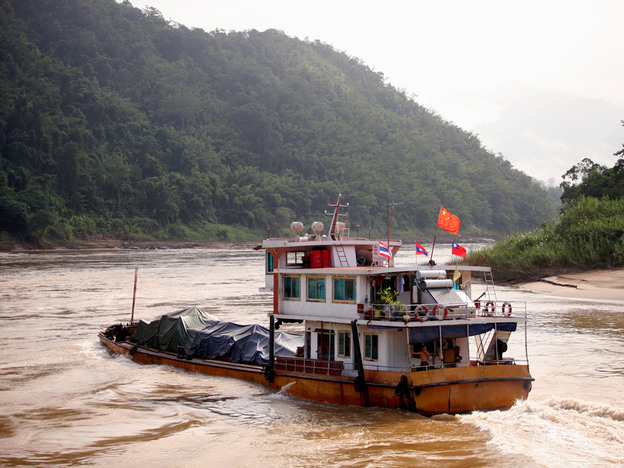 A cargo ship heads upstream toward China on the Mekong River in Myanmar. The river flirts with Myanmar for about 120 miles, mostly along the border it shares with Laos.