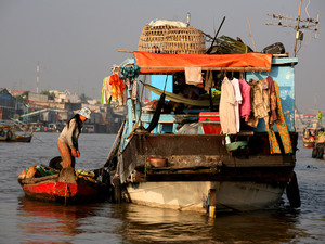 A woman stands near houseboat in Chau Doc, Vietnam.