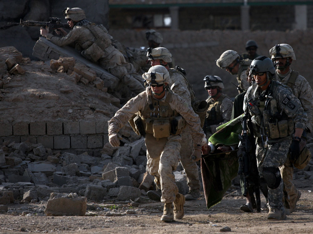 An Army flight medic and U.S. Marines carry a wounded Taliban on a stretcher amid a firefight