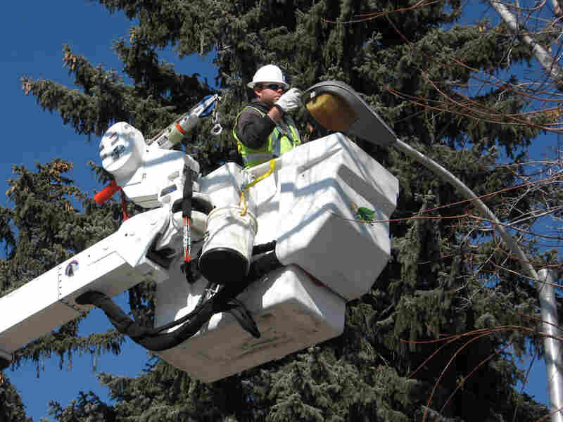 A utility worker turns off a Colorado Springs street light. Jeff Brady/NPR