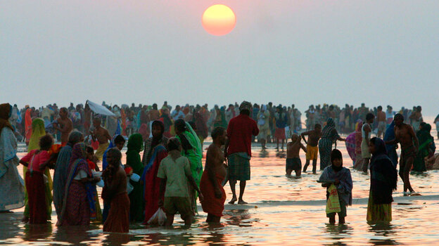 In this file photo from Jan. 14, 2008, Hindu devotees wade on Sagar Island, site of annual religious festivals that draw hundreds of thousands of visitors. The 20-mile-long island is shrinking at an accelerating pace. (AP)
