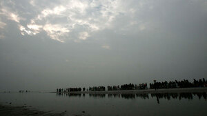 Pilgrims take a holy dip at a lagoon on the occasion of Makar Sankranti at Gangasagar on Sagar Island, the confluence of the Ganges River and Bay of Bengal, on Jan. 14. A scientist says the sacred island has shrunk by nearly 10 square miles in the past 40 years, displacing thousands of people.