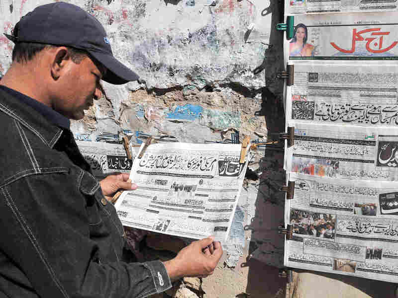 A Pakistani man reads a newspaper headline about the capture of a top Taliban commander.