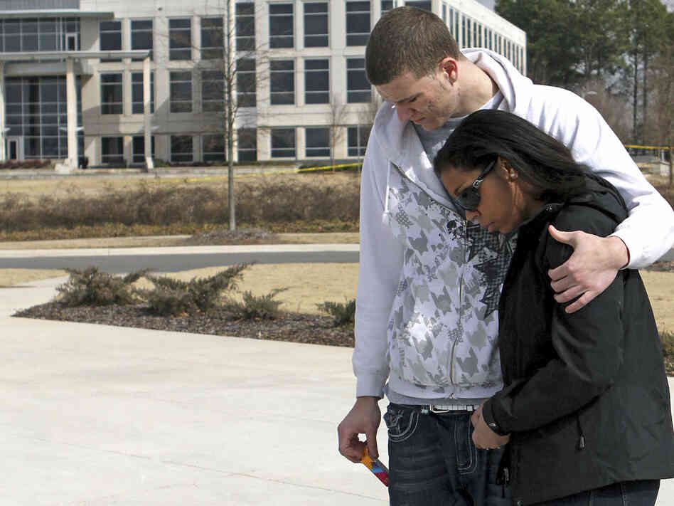 Mourners at the University of Alabama comfort one another after the fatal shooti