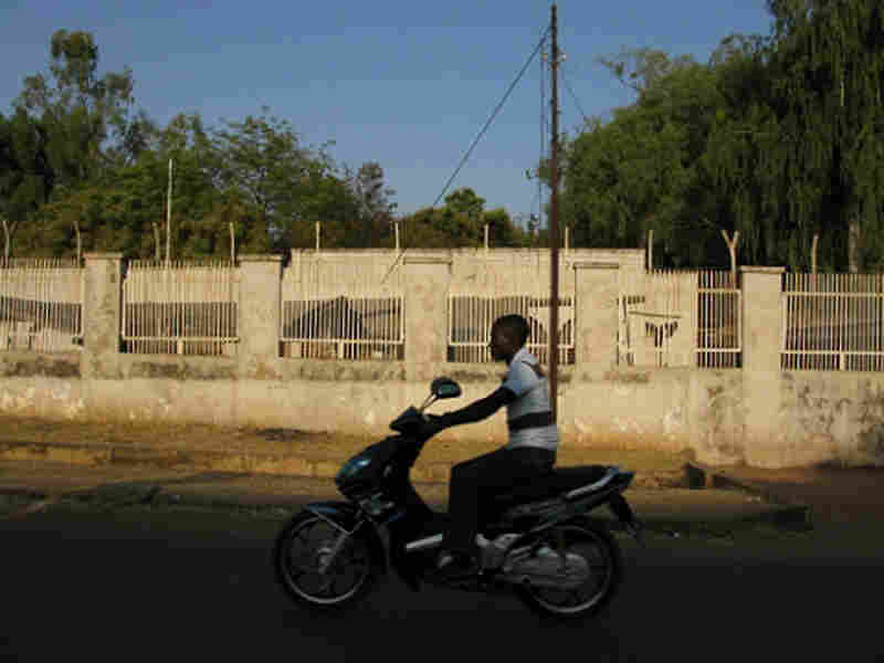 Motorcyclist drives in front of an abandoned American consulate compound.