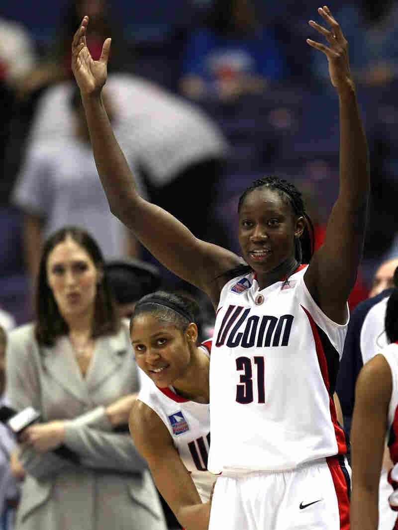 Maya Moore peeks around teammate Tina Charles as the Connecticut Huskies celebrate victory.
