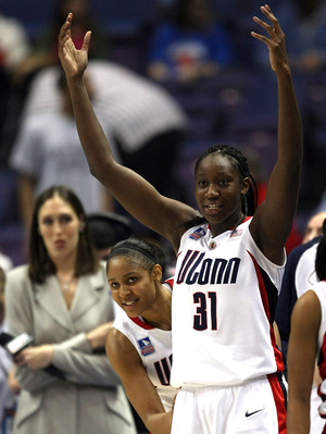 Maya Moore peeks around teammate Tina Charles as the Connecticut Huskies celebrate victory.