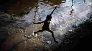 A girl jumps across a flooded field in Port-au-Prince.
