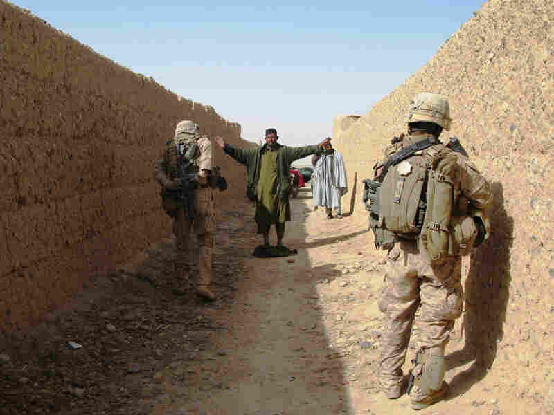 A Marine prepares to search an Afghan man.