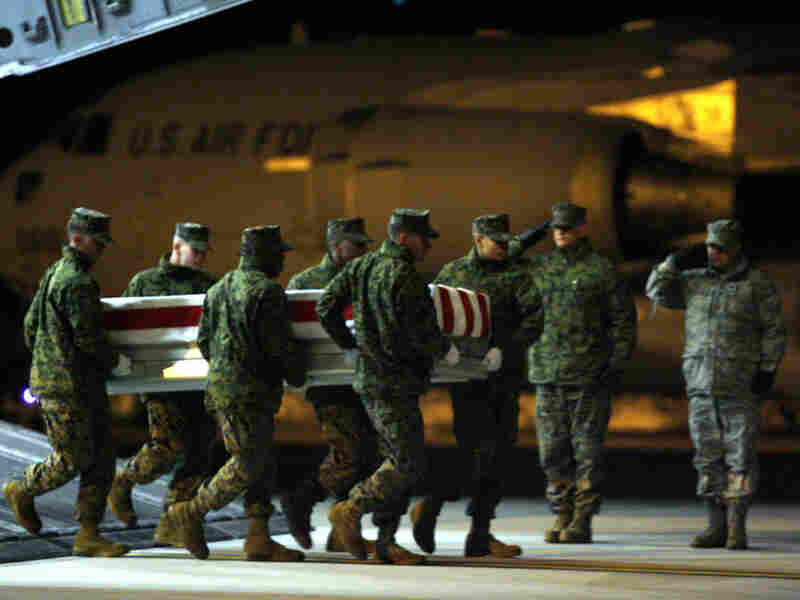 A team of Marines carries the transfer case containing the remains of Yazzie upon arrival at Dover.