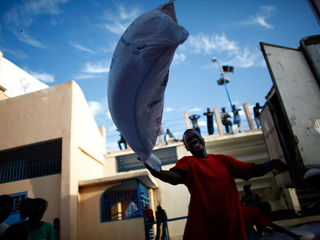 Bags of rice donated by the United States are thrown off a truck and handed out to women standing in a food distribution line at the main soccer stadium in Port-au-Prince. (NPR)