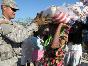U.S. soldier hands out sacks of rice to Haitians in Cite Soleil