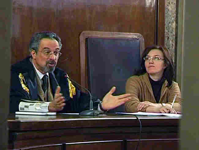 Judge Oscar Magi, left, flanked by an aide, speaks in a court room in Milan, Italy.