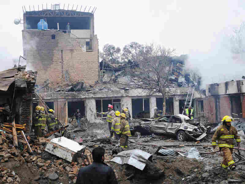 Afghan firemen gather to inspect the debris at the site of a blast in the heart of the capital.