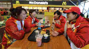 Chinese short-track speedskaters eat in the dining hall during a media tour of the Olympic Village.