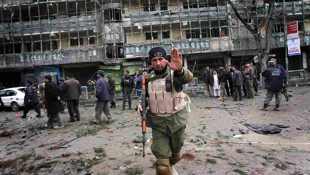 An Afghan security officer patrols outside the shattered Park Residence guesthouse in Kabul.