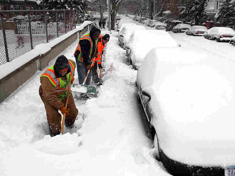 Workers clear an overpass of snow in New York City