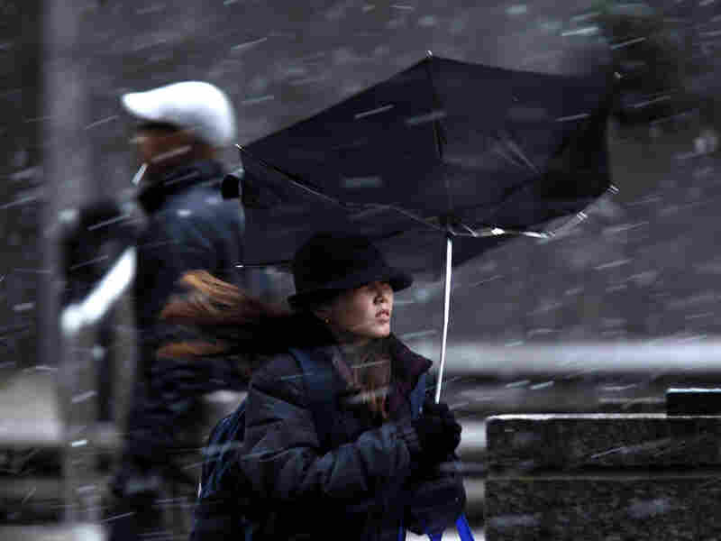 A woman's umbrella was turned inside out from a gust of wind during a winter storm in Philadelphia.